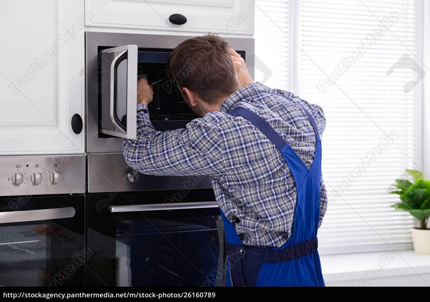 Man Repairing Microwave Oven Royalty