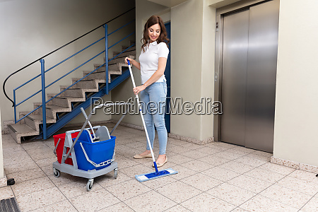female janitor cleaning floor with mop