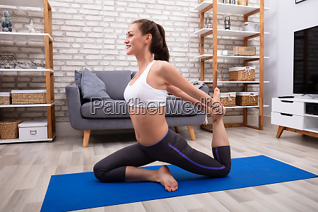 young woman doing stretching exercise on