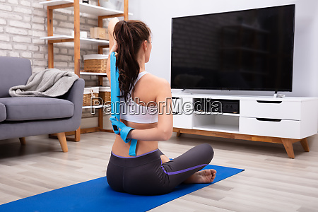 fit woman exercising with yoga belt