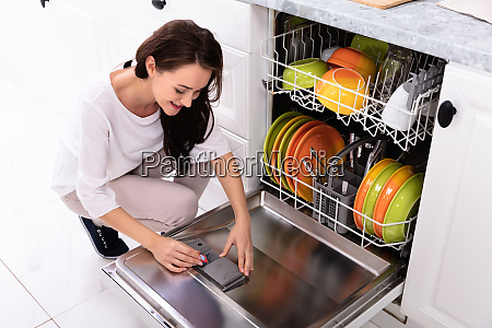 woman putting soap tablet in dishwasher