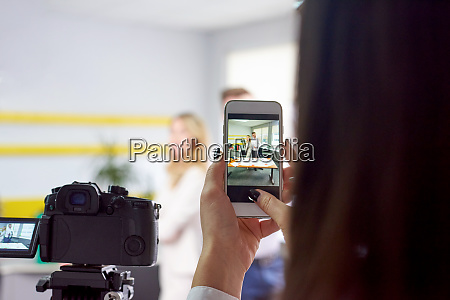 woman taking photo of business partners