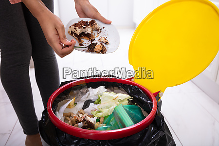 woman throwing cake in trash bin