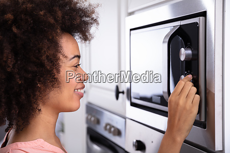 woman adjusting temperature of microwave oven