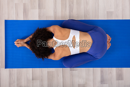 woman doing yoga on fitness mat