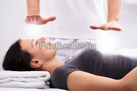 young woman receiving reiki treatment by