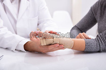 doctor checking fractured hand of a