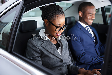 two businesspeople traveling by car