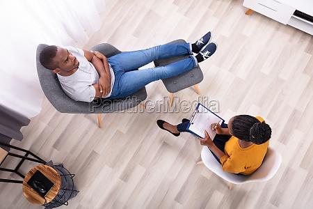 man sitting on chair near psychologist