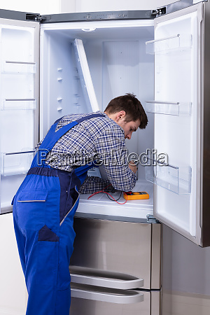 serviceman checking fridge
