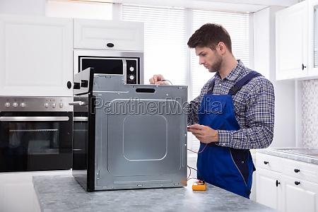 male repairman repairing oven