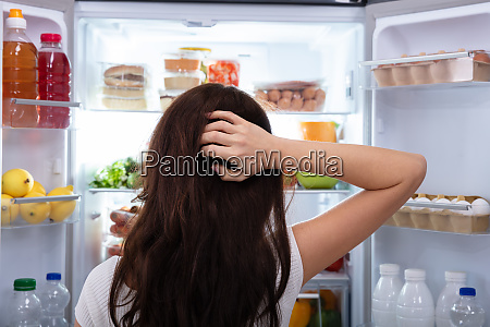 woman searching for food in refrigerator