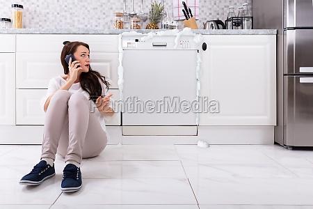 sad woman sitting next to damaged