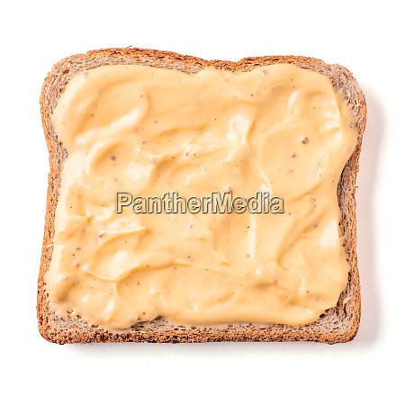 bread slice with mustard sauce isolated