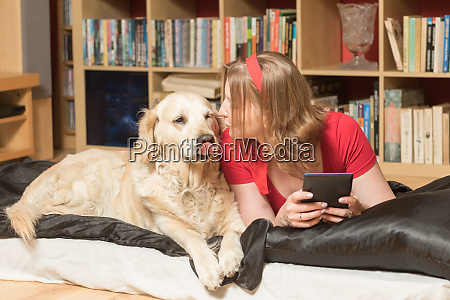 young woman is kissing her dog