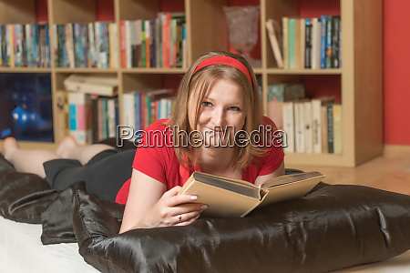 smiling young woman is reading a