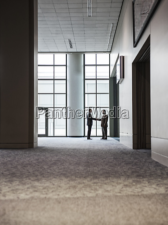 two businessmen silhouetted and shaking hands