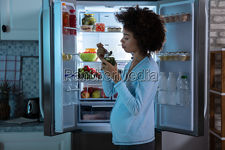 pregnant woman eating pickle from jar