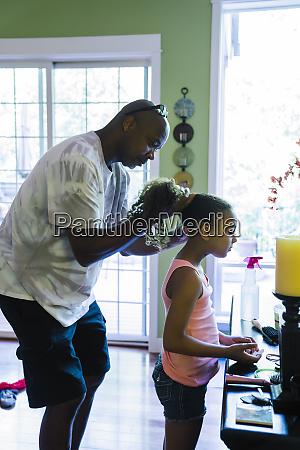 dad fixing daughters hair