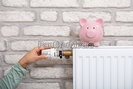 person adjusting thermostat with piggy bank