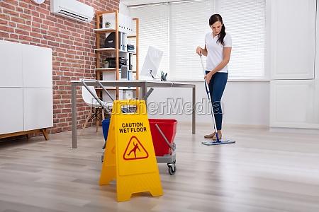 woman cleaning hardwood floor in office