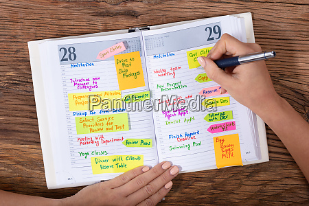 businesswoman writing schedule in diary with