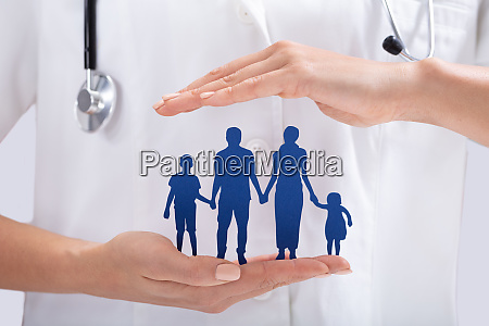 doctors hand holding family paper cut