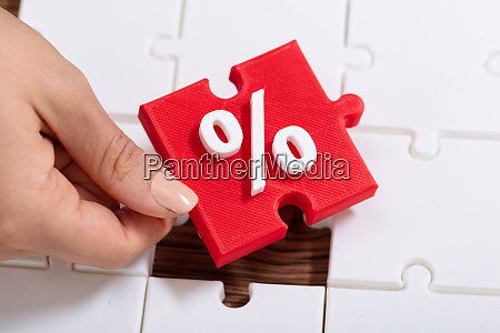 hand holding jigsaw puzzle with percentage