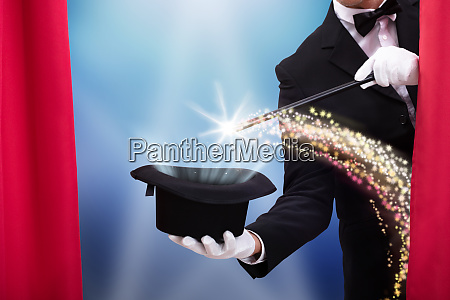 magicians hand with wand and hat