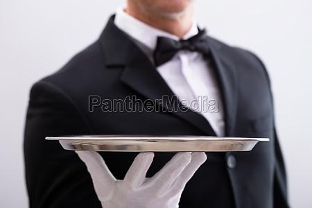 waiters hand holding empty tray