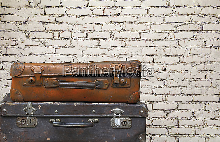 old vintage travel suitcases over brick