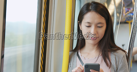 woman using smart phone on train
