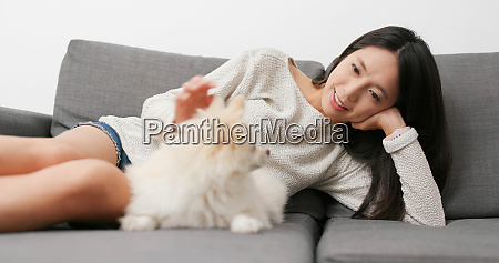 woman caressing her dog at home