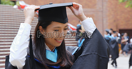 woman wearing graduation gown and mortarboard