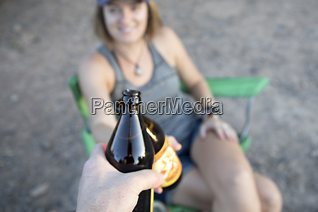 a woman cheers a beer at