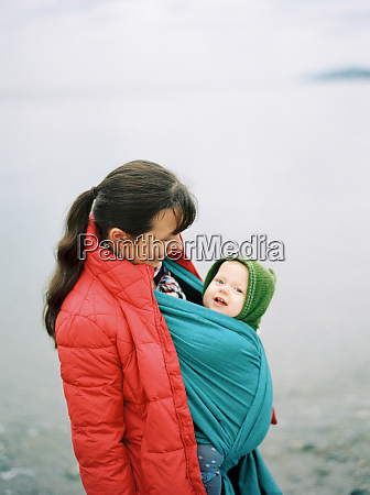 mother standing outdoors with baby in
