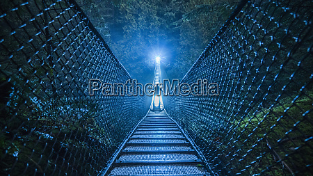 mysterious silhouetted person on suspension bridge