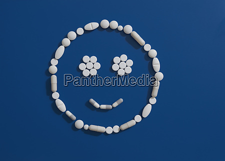 pills forming smiley face on blue