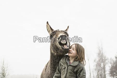 playful girl and donkey