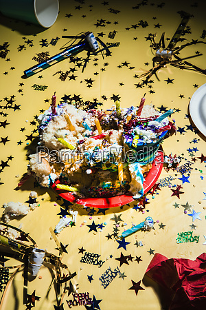 messy birthday cake and confetti on