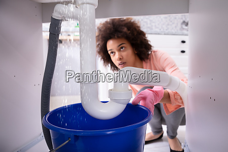 woman looking at water leaking from