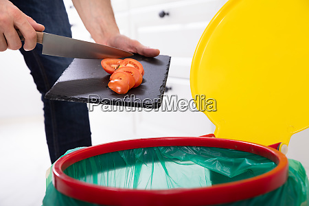 man throwing tomatoes slice in trash