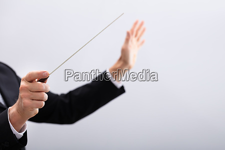 music conductor hands holding baton