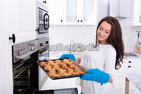 woman removing tray with baked croissants