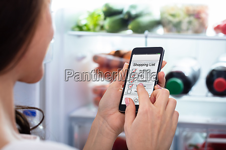 woman marking shopping list on mobile