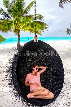 beautiful woman relaxes on a swing