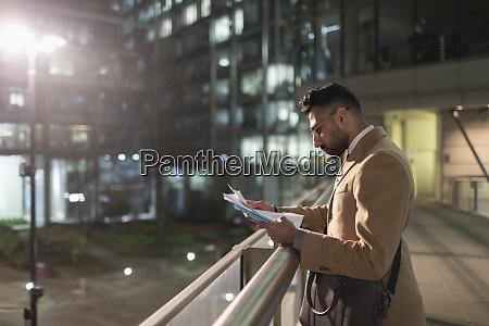businessman reviewing paperwork on urban pedestrian