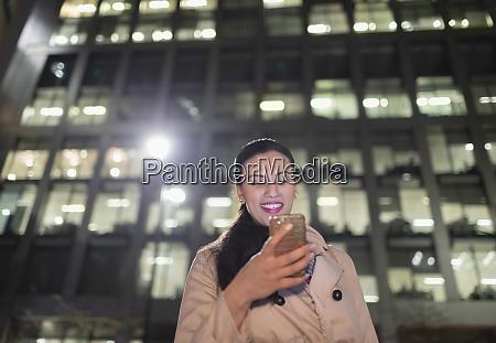 smiling businesswoman using smart phone below