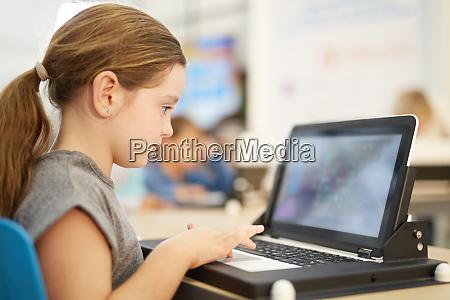 girl playing game on laptop