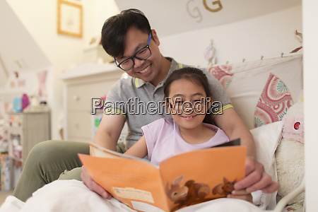 father and daughter reading book in